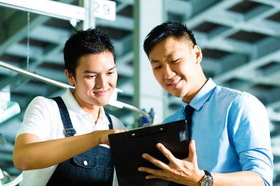 Worker or sales manager and owner, ceo or controller, look on a Clipboard in a factory