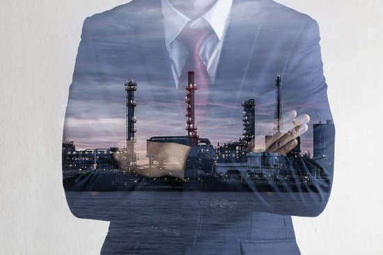 Double exposure image of Business man with petroleum oil refinery plant beside river. Crude Oil Process machinery